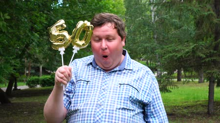 felicitação : Big man holding golden balloons making the 50 number outdoor. 50th anniversary celebration party Stock Footage