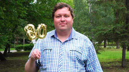 felicitação : Big man holding golden balloons making the 80 number outdoor. 80th anniversary celebration party