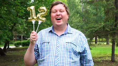 двенадцать : Big man holding golden balloons making the 12 number outdoor. 12th anniversary celebration party