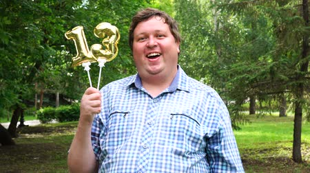felicitação : Big man holding golden balloons making the 13 number outdoor. 13th anniversary celebration party