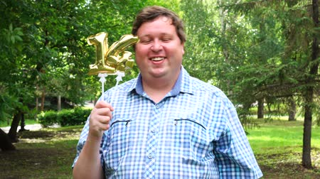 felicitação : Big man holding golden balloons making the 14 number outdoor. 14th anniversary celebration party