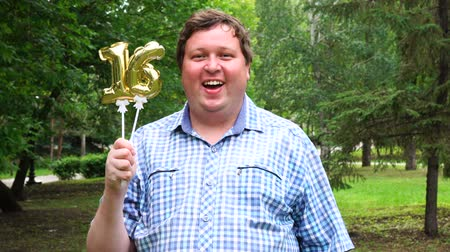 felicitação : Big man holding golden balloons making the 16 number outdoor. 16th anniversary celebration party Stock Footage