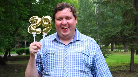 felicitação : Big man holding golden balloons making the 29 number outdoor. 29th anniversary celebration party