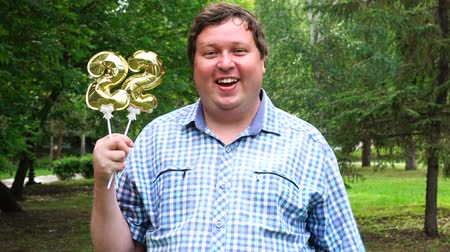 felicitação : Big man holding golden balloons making the 22 number outdoor. 22th anniversary celebration party