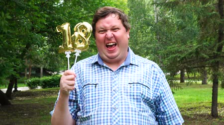 osiemnastka : Big man holding golden balloons making the 18 number outdoor. 18th anniversary celebration party Wideo