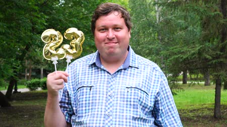 felicitação : Big man holding golden balloons making the 23 number outdoor. 23th anniversary celebration party Stock Footage