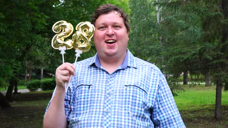 felicitação : Big man holding golden balloons making the 28 number outdoor. 28th anniversary celebration party Stock Footage