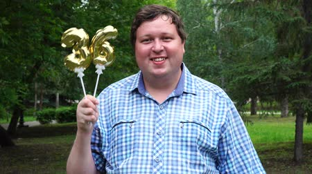 otuzlu yıllar : Big man holding golden balloons making the 36 number outdoor. 36th anniversary celebration party Stok Video
