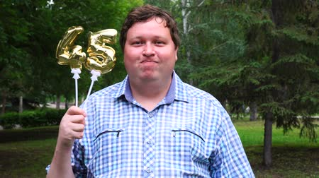 felicitação : Big man holding golden balloons making the 45 number outdoor. 45th anniversary celebration party Stock Footage