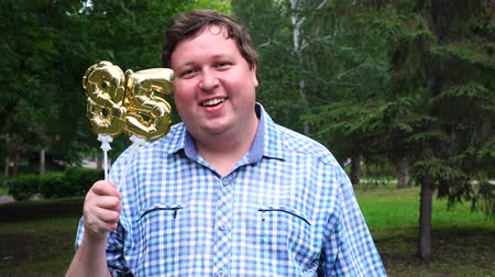 felicitação : Big man holding golden balloons making the 85 number outdoor. 85th anniversary celebration party Stock Footage