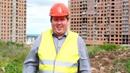 realty : Male builder foreman, worker or architect on construction building site standing while laughing and smiling to camera Stock Footage