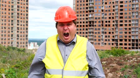 panico : Male builder foreman, worker or architect on construction building site is shouting and looking to camera Filmati Stock