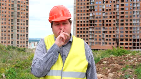 realty : Builder on construction building site making a shushing gesture raising his finger to his lips as he asks for silence