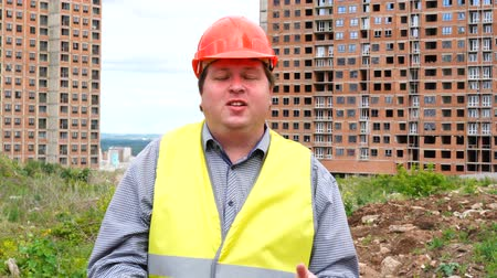 hat : Male builder foreman, worker or architect on construction building site talking about something Stock mozgókép
