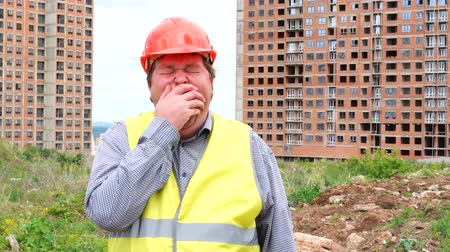 ziewanie : Tired male builder foreman, worker or architect on construction building site yawning Wideo