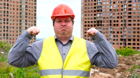 güvenilirlik : Young caucasian fat man on construction site background, shows power and muscle, guarantees reliability and results