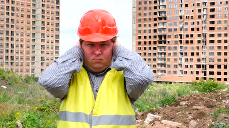 realty : young handsome builder is afraid (man covers his ears with hands) - construction site