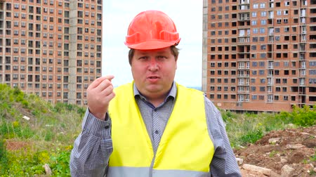 realty : Have a money concept. Builder making cash sign gesture rubbing fingers together on construction site background