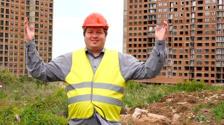workman : Male builder foreman, worker or architect on construction building site proudly shows results while raising his arms