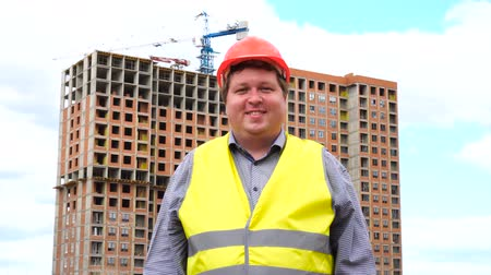 средства : Male builder foreman, worker or architect on construction building site smiling to camera Стоковые видеозаписи