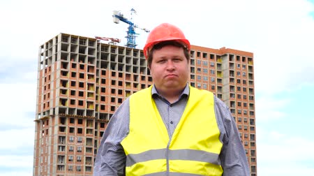 hat : Young builder says No. By shaking his head. Worker says No, meaning No. Construction site Stock mozgókép