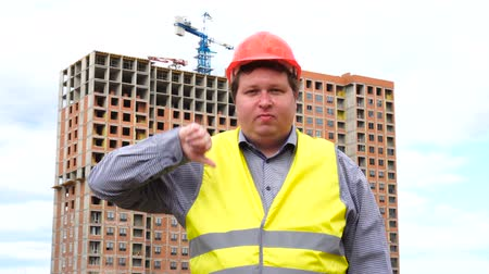прораб : Male builder foreman, worker or architect on construction building site showing thumb down and looking to camera