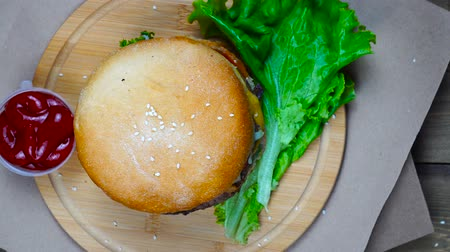 sezam : Top view of fresh appetizing hamburger rotating on wooden plate Wideo