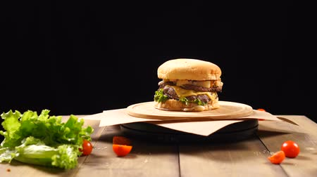 кунжут : Fresh appetizing hamburger rotating on black background.