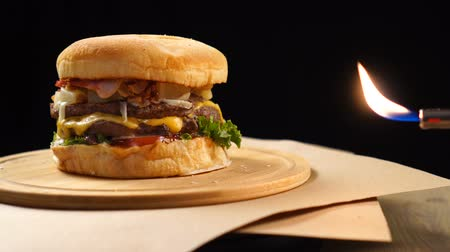 sajtburger : Fresh appetizing hamburger rotating on black background near real fire