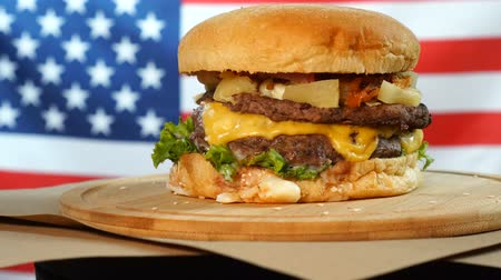 sezam : Grilled American beef burger with lettuce, cheese, onion served on pieces of brown paper rotating on a wooden counter. Wideo