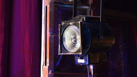 akt : vintage theater spotlight on black curtain with dust floating in front