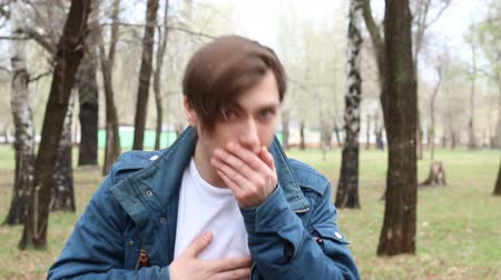 coughing : Portrait of handsome caucasian young man who is sneezes in the park