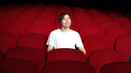theater hall : man sitting alone in empty cinema hall or theater and watching performance or movie