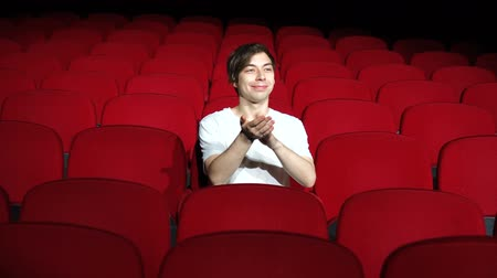 初演 : man sitting alone and applauding in empty cinema hall or theater
