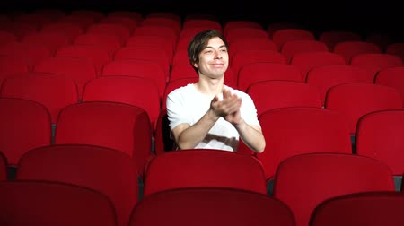 премьера : man sitting alone and applauding in empty cinema hall or theater