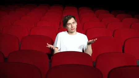 初演 : man sitting alone in empty cinema hall and displeased