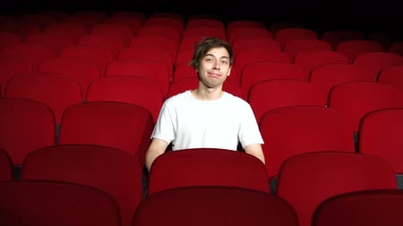 premiere : Man sitting alone in empty cinema hall or theater