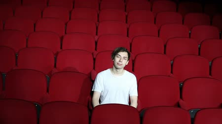 初演 : Man sitting alone in empty cinema hall or theater