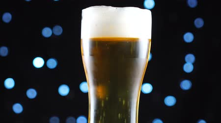 ale : Light Beer close-up. Pint of cold light beer isolated on matte black background, rotation
