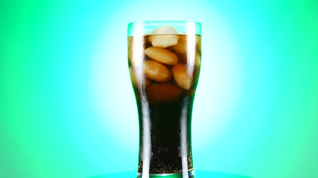 limonádé : Glass of cola turns slowly around its axis. Close up 4K video. Green background. Stock mozgókép