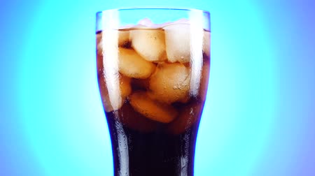 cola : Glass of cola rotating slowly around its axis. Close up 4K video. Blue background.