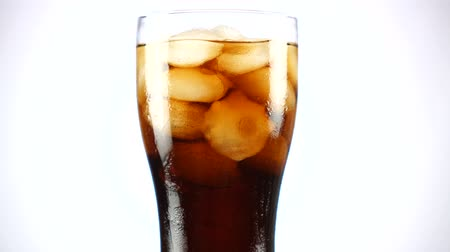cola : Glass of cola turns slowly around its axis. Close up 4K video. White background.