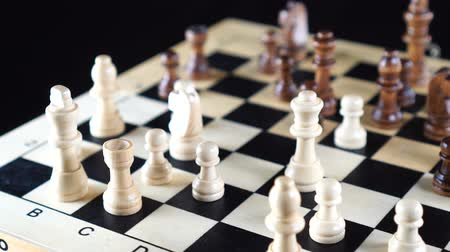 cavaleiro : Slow tracking shot behind chess pieces on wooden chess board