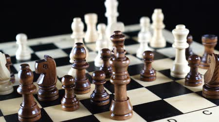 cavaleiro : Chess board turns slowly around its axis. Close up 4K video. Black background