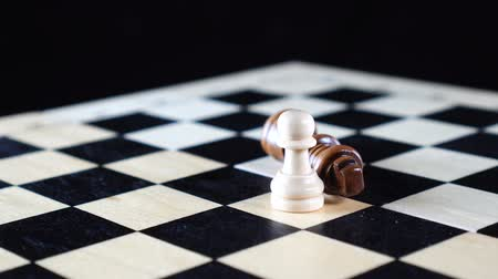 стратегический : Two chess pawn and king with the vanquished black chess piece lying on its side and the white pawn standing upright Стоковые видеозаписи