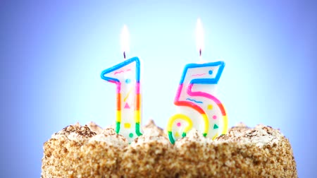 gênero alimentício : Birthday cake with a burning birthday candle. Number 15. Background changes color Stock Footage