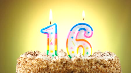 gênero alimentício : Birthday cake with a burning birthday candle. Number 16. Background changes color Stock Footage