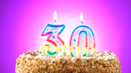 otuzlu yıllar : Birthday cake with a burning birthday candle. Number 30. Background changes color Stok Video