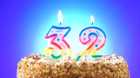 gênero alimentício : Birthday cake with a burning birthday candle. Number 32. Background changes color Stock Footage