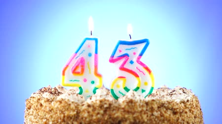 gênero alimentício : Birthday cake with a burning birthday candle. Number 43. Background changes color Stock Footage